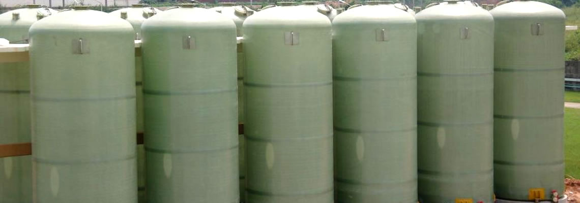 There are a few large nature color FRP tanks in the same size standing on the ground.
